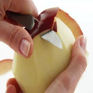 دست ها در حال سیب پوست کندن با چاقو