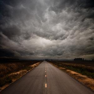 جاده ای منتهی به افق در هوای ابری و طوفانی
