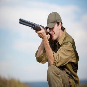 مردی در حال نشانه گرفتن هدف با اسلحه با یک چشم بسته و یک پا خم شده روی زمین
