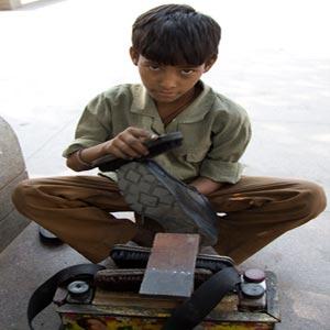 پسر در حال واکس زدن کفش همراه با وسایل و جعبه واکس